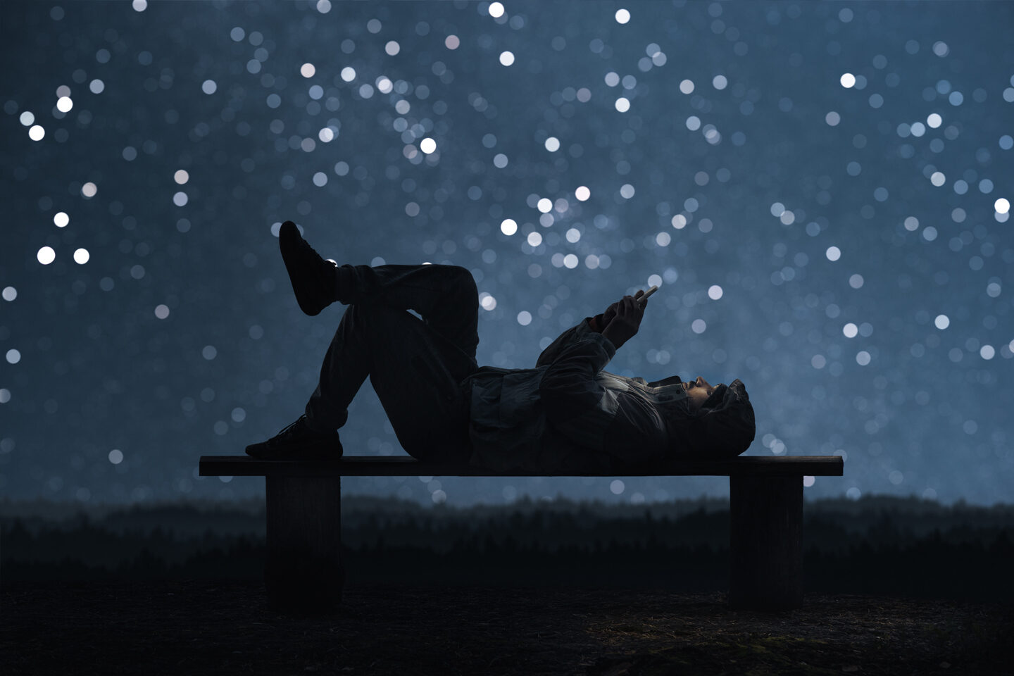 Man-with-phone-under-starlit-sky